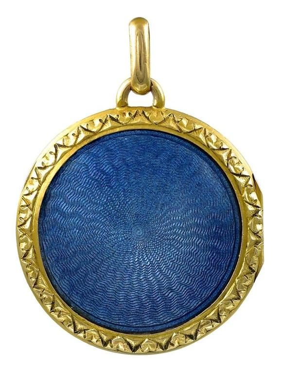 "Exquisite antique locket, with double-sided french blue guilloche enamel.  18K yellow gold.  On the front is a beautiful basket of flowers, tied with a ribbon.  Intricate engraved border front and back.  1 1/8"" in diameter.  Alice Kwartler has"
