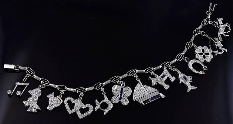 One-of-a-kind antique platinum charm bracelet.  Set with thirteen platinum charms: one is prettier than the next!  (Most unusual because these bracelets usually have some undistinguished charms.)  The charms are encrusted with diamonds, rubies and