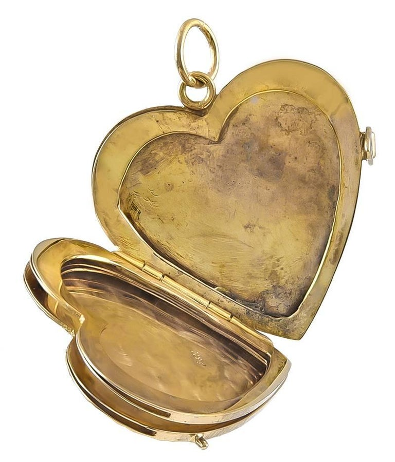 """Beautiful heart locket.  14K yellow gold.  Front has a matte finish, with shiny gold floral and leaf engraving.  14K yellow gold.  Opens to reveal bezels for four pictures.  1 1/4"""" x 1 1/4.""""  A timeless and romantic piece of"""
