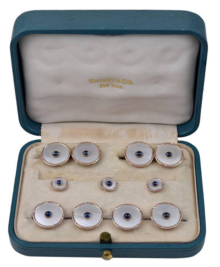 Antique men's dress set.  Made and signed by TIFFANY & CO.  14K yellow gold, with mother-of-pearl centers. Applied cabochon sapphire in middle of each piece.  A classic 9-piece set: two double-sided cufflinks,  four vest buttons and three studs.  In