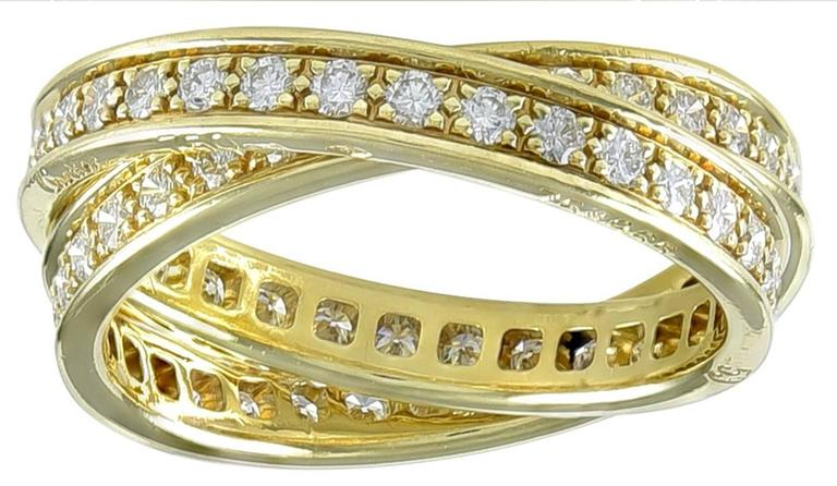 Graceful elegant two-band eternity ring. Made, signed & numbered by Cartier. 18k yellow gold, fully set with round brilliant diamonds. Size 7. Unusual with two bands; no longer made by Cartier.