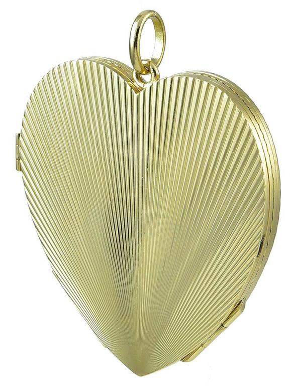 Best ever four-picture figural heart locket. Opens to a large four-leaf clover. Deep deco lines engraved front and back. Heavy gauge 18K yellow gold weighing 64 grams. 2