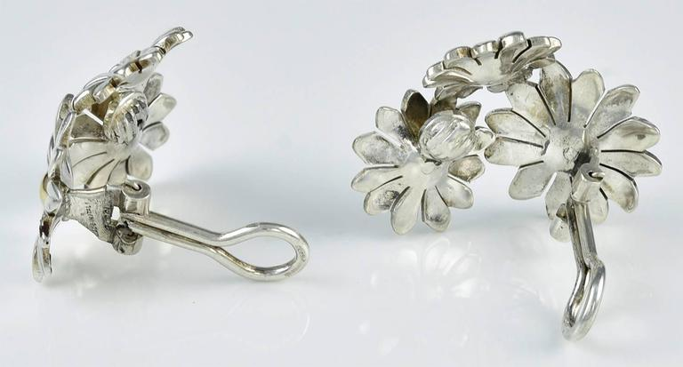 """Very attractive ear clips, made and signed by GUCCI.   Figural sterling silver daisies, set with 18K gold centers.   The earrings have a """"left"""" and """"right"""" side, to frame the face.  Very graceful.  Omega clip.  Alice Kwartler has sold the finest"""