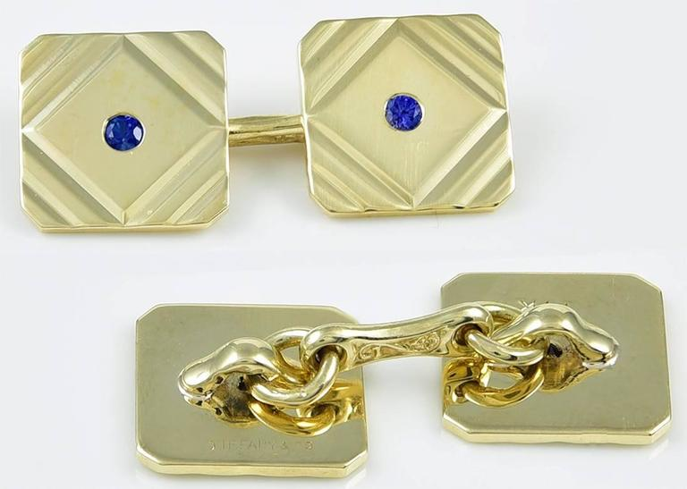 Classic Art Deco double-sided cufflinks.  Made and signed by TIFFANY & CO.   14K yellow gold, with diagonal line cut corners and center faceted sapphires.   1/2