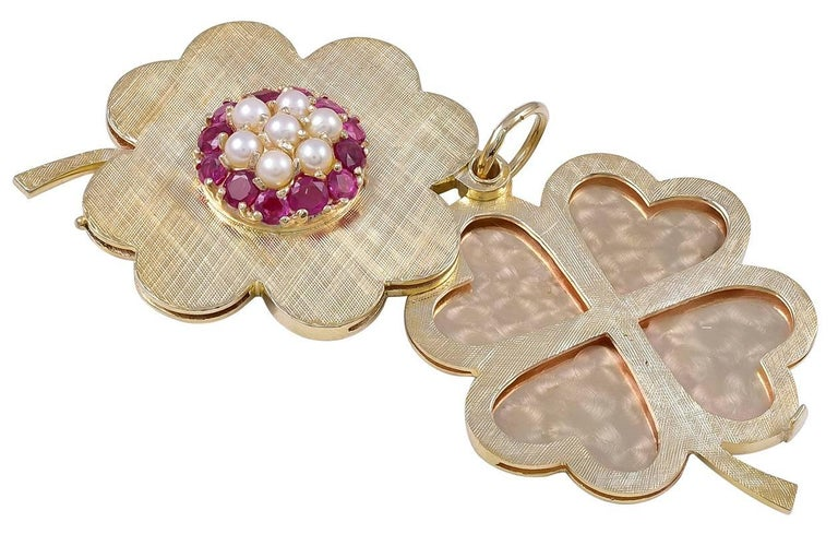 """Large figural """"four-leaf clover"""" locket.  With a central applied cartouche of brilliant faceted rubies and seed pearls.  Opens to reveal eight heart-shaped bezels.  Almost impossible to find lockets for eight picture.  Heavy gauge textured"""