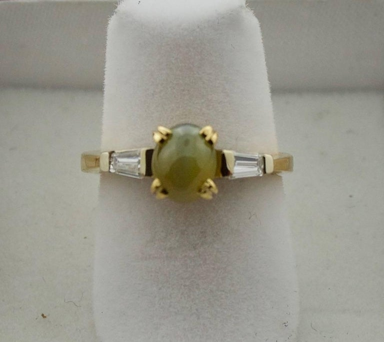 Cats-Eye and Diamond Ring in 18k  One Fine Chrysoberyl Cats Eye weighing 1.80 carat Two Tapered Baguette Cut Diamonds weighing .35 carats The Picture with The