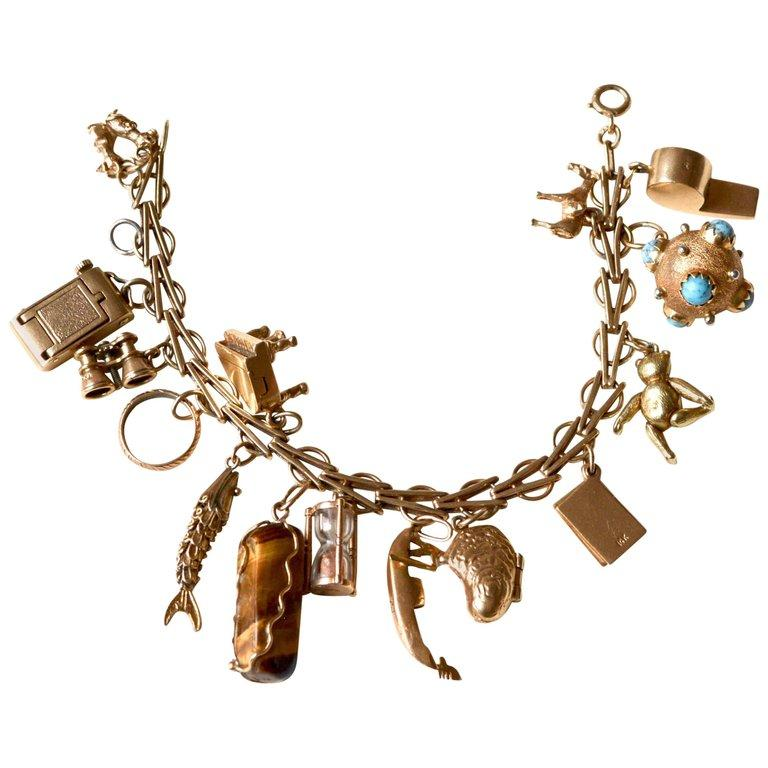 1950s-60s 14k gold charm bracelet with various unique charms. Most have movement, which is rarer. Highlights being the camera, clam with pearl, and piano. There is also a large Etruscan charm. The bracelet itself is a unique, possibly custom make.