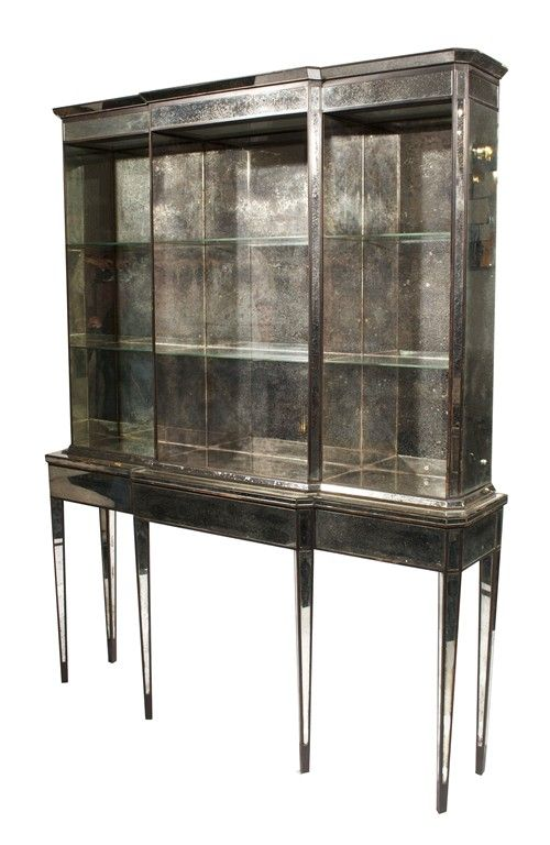 Rare and exceptional mirrored breakfront by Syrie Maugham. Glass shelves in a mirrored, illuminated case atop a mirrored, six leg console. Mercury glass mirror shows beautiful age and patina. Descended through original owners – the Grace and Phipps
