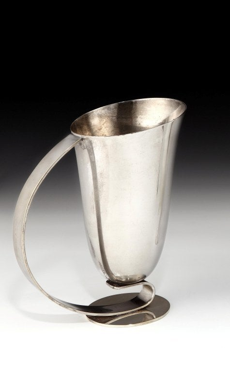 A stylish and important Modernist-style cocktail pitcher, the vessel resting upon an elongated curved handle and circular foot, signed 'DESNY PARIS'.  The firm of Maison Desny (1927 - 1933) was located at Avenue des Champs Elysées in Paris from