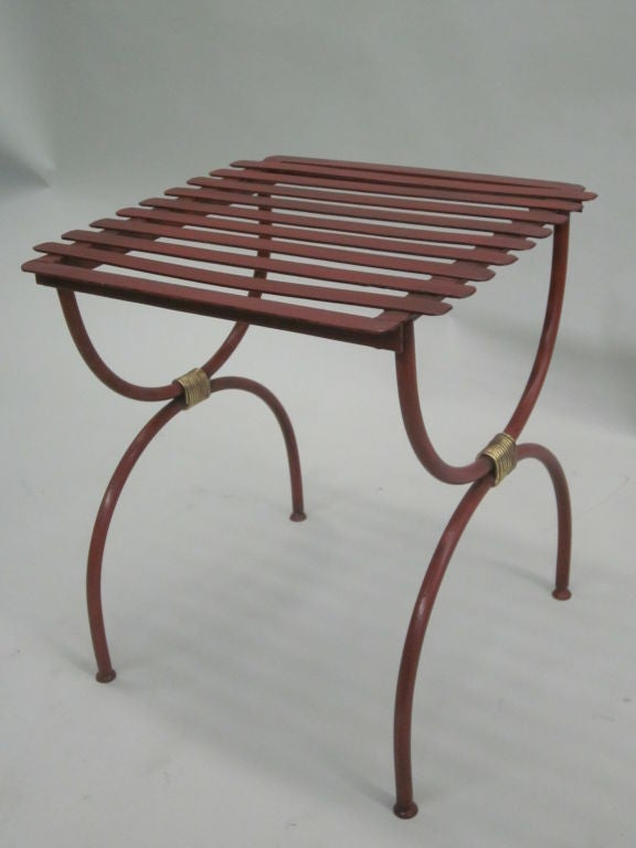 Two elegant pair of French Mid-Century wrought iron curile X-form end tables or luggage racks in the modern neoclassical aesthetic. Each is lacquered Chinese red with gilt iron wrappings uniting the upper and lower parts. It is possible to use these