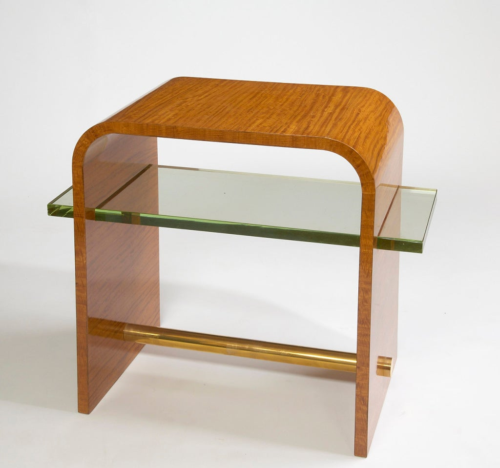 Jacques Adnet (1901-1984). Side table in satinwood with original clear glass shelf, gilt bronze mounts. France, 1930s. Dimensions: 30 x 16 x 25 H.