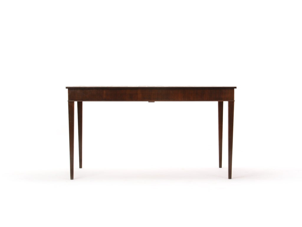 A rosewood dining table with a tiled top, tapered legs, and 2 (17.75