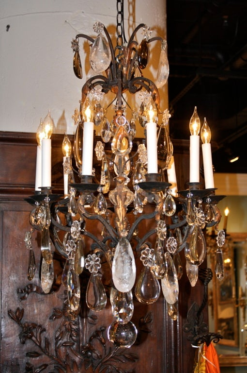 French wrought iron chandelier in the Louis XV style with gilt-tole foliate elements and many large and unusual crystal pendants.  There are large oblong cut rock crystals and half-pear rock crystals.  Two crystal balls.  The chandelier with be