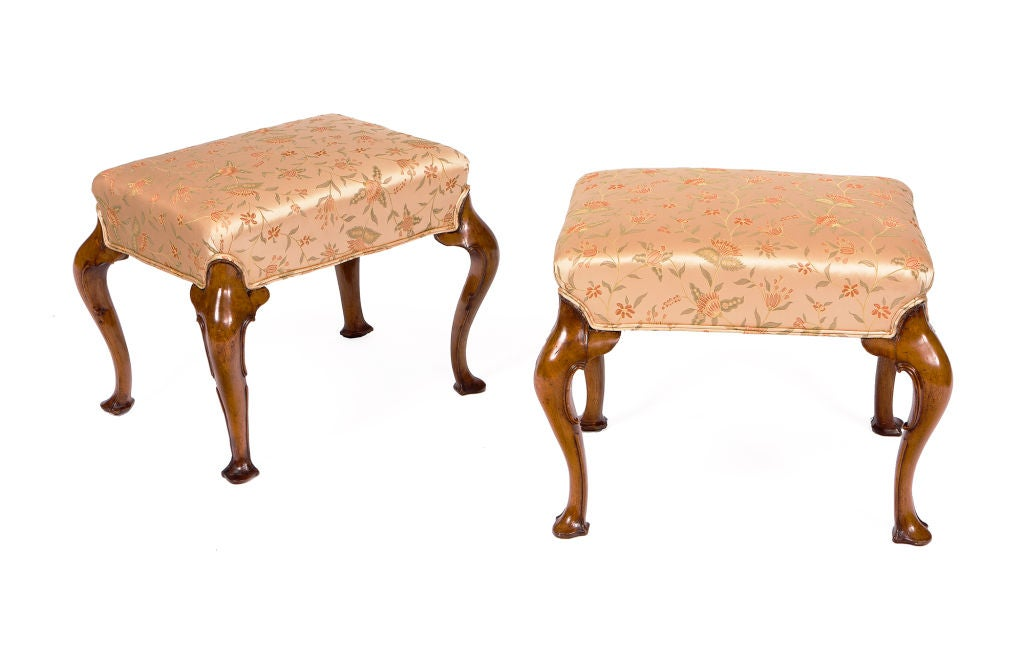 Pair of walnut stools with cabriole legs and trifid feet. With an exaggerated curve to the legs and the edges carved with C-scrolls.