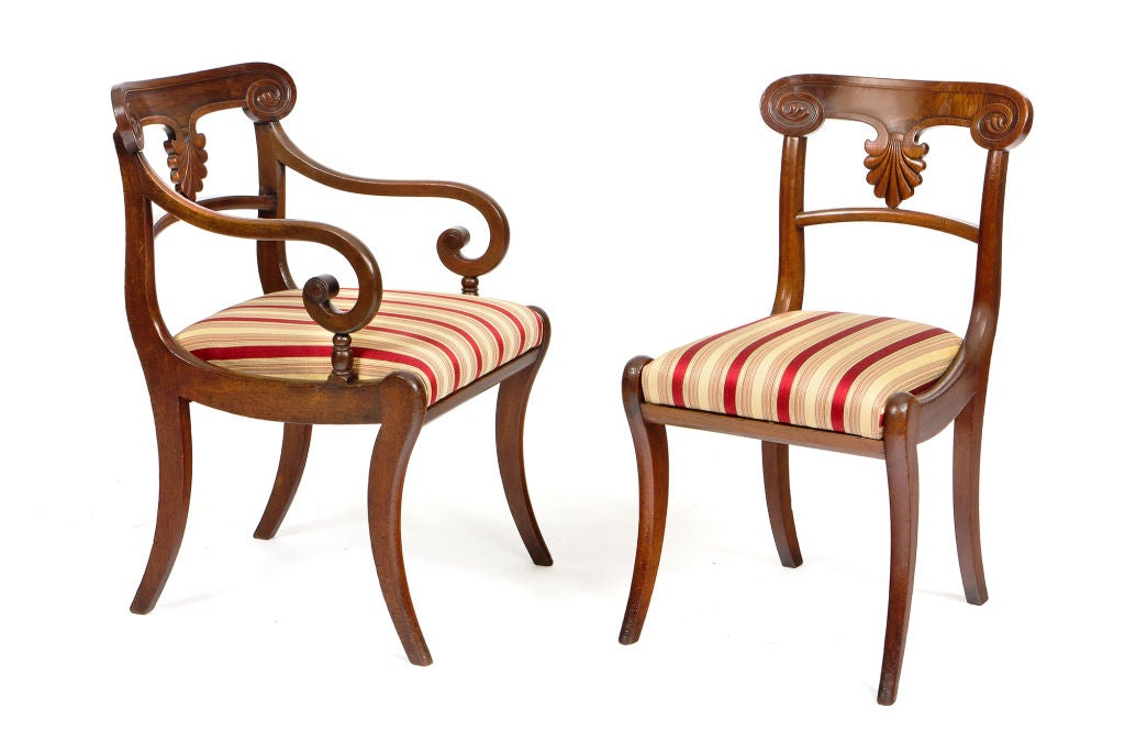 Set of 20 early 19th century Regency mahogany dining chairs. Each with a scroll-carved crestrail over a carved palmette splat and a drop-in seat. Raised on front and back saber legs.  Armchairs: 33 1/2