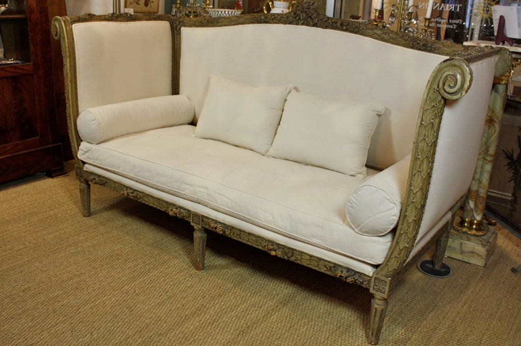French carved wood sofa, with lovely rose and garland, acanthus, ribbon and other neoclassical detailing. Newly-upholstered in which muslin with separate seat cushion and four pillows. Paint appears to be original.