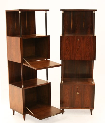 Two vertical Rosewood bars that could also be used as cabinets custom-made by Joaquim Tenreiro. There is display space for bottles or books and tapered Rosewood feet. Each cabinet features a pair of vintage lock boxes with prominent grain which are