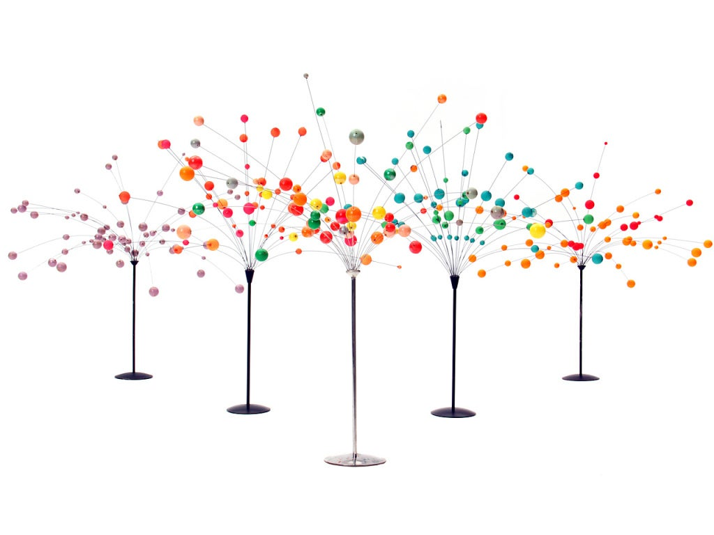 A kinetic sculpture comprised of variegated balls on undulating wire rods flowing from a lacquered metal pedestal. A selection is available in varied colors.