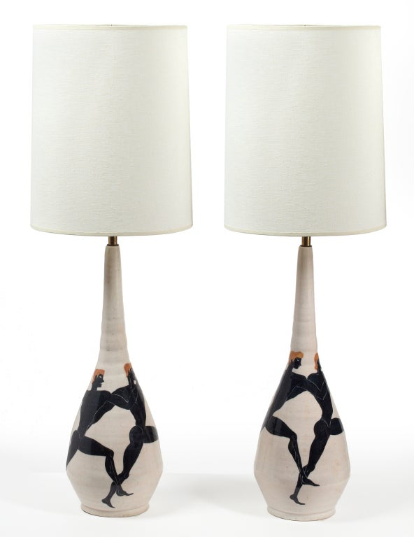 A unique pair of tall ceramic table lamps, hand thrown and hand-painted with Olympian figures in black on a white glazed ground. Each signed to the base. By Ernestine. Italian, 1954.