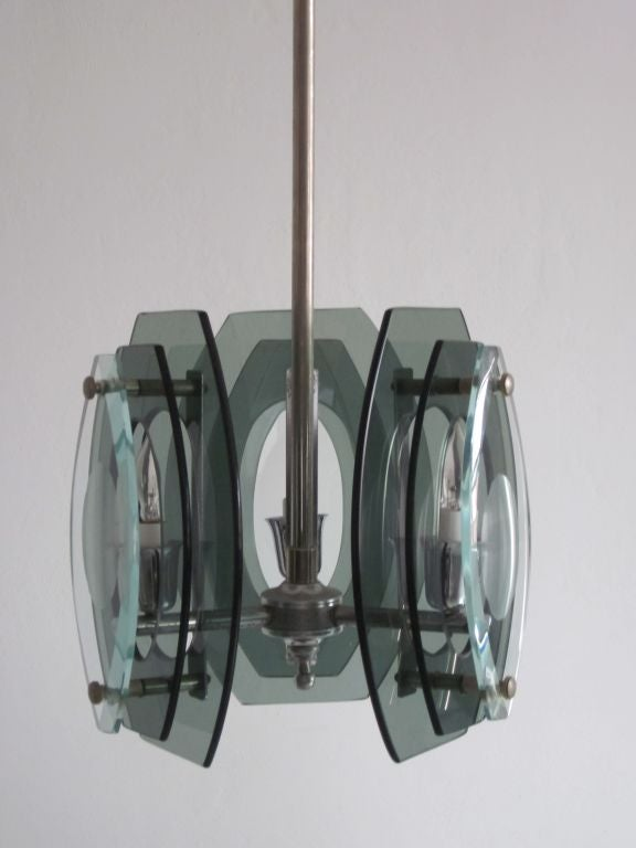Italian Mid-Century Modern smoked and green glass pendant, lantern or chandelier in the style of Max Ingrand and Fontana Arte.   The three-light fixtures has each lighting element encased by three successive layers of glass, the two inner levels