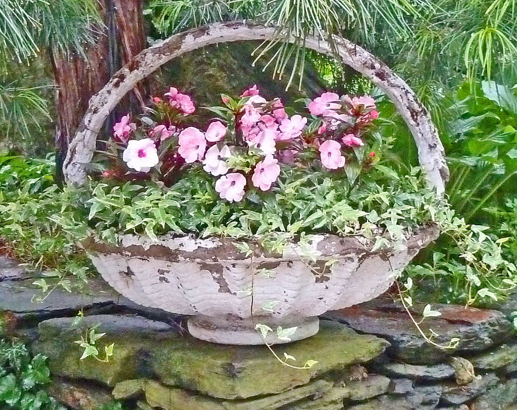 Large round Jardiniere in the form of a woven basket.  A lovely accent in the garden or even as a table centerpiece
