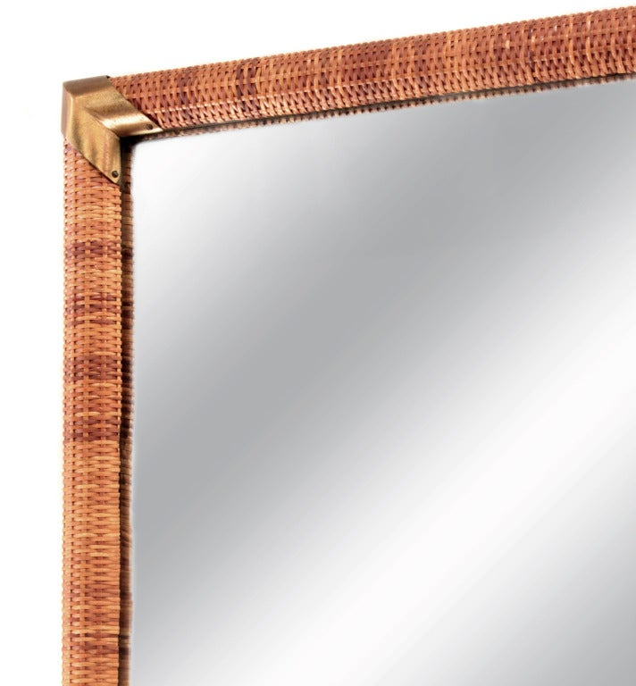 Wall-hanging mirror with cane wrapped frame and brass accents by T.H. Robsjohn-Gibbings for Widdicomb, American, 1950s.