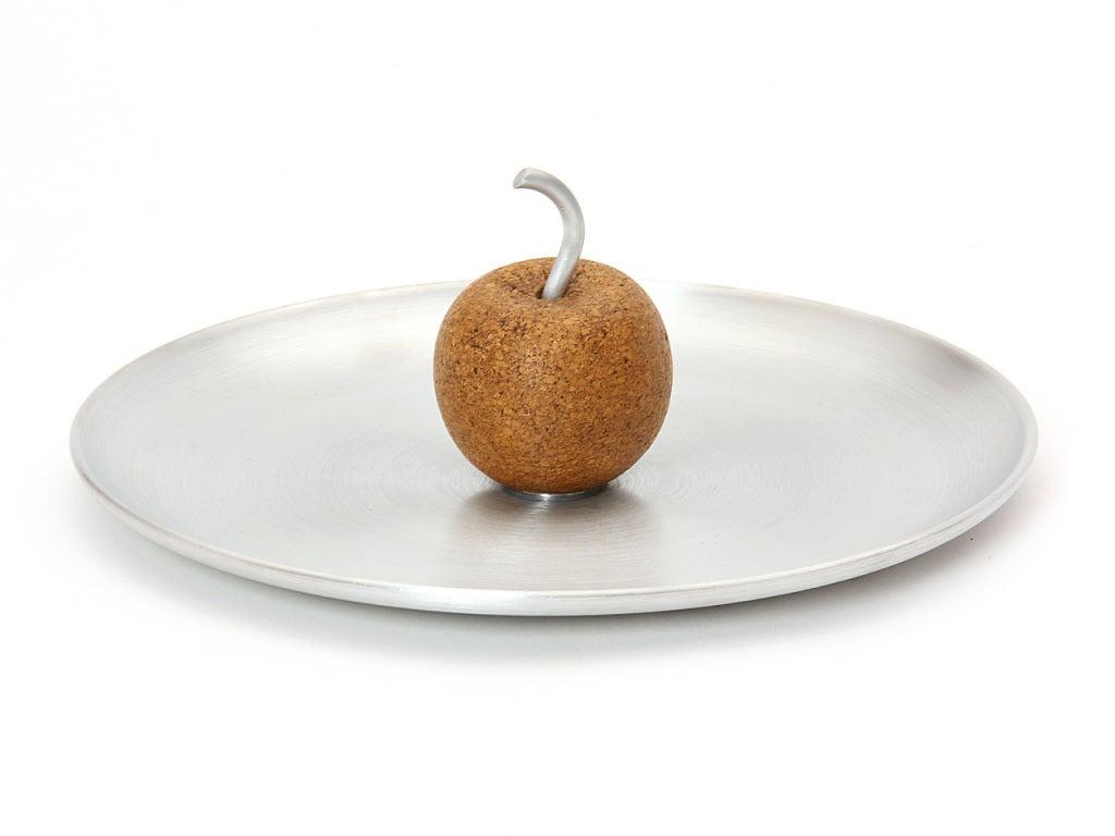A spun aluminum tray with cork apple and aluminum stem.