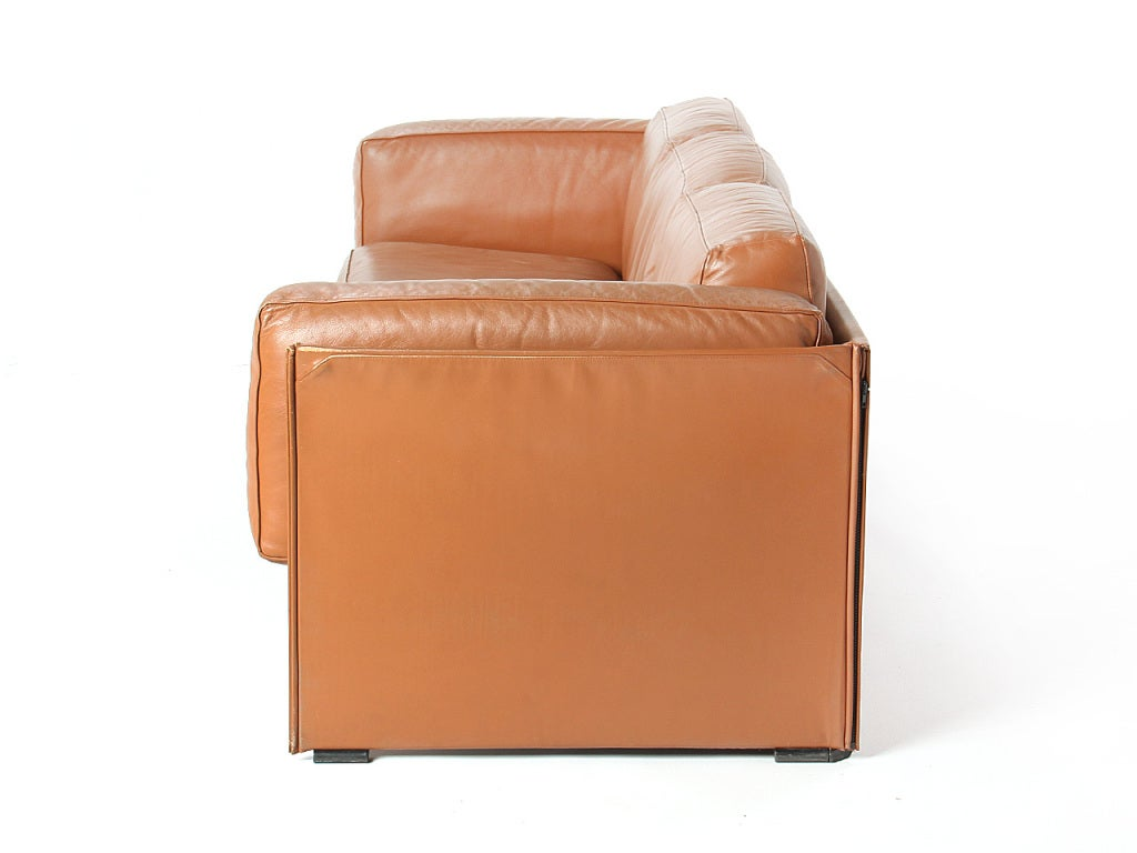 A brown leather 'Duc' three-seat sofa with exposed leather wrapped frame.