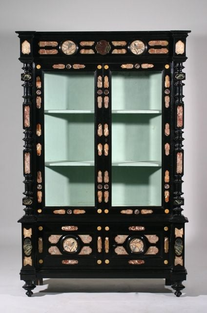 An Italian Third Quarter 19th Century Baroque Style Marble Inset and Pietra Dura Inlaid Ebonised Cabinet; the moulded top above a fretwork carved case with marble and glass on the front and both sides, above two cabinet doors decorated with four