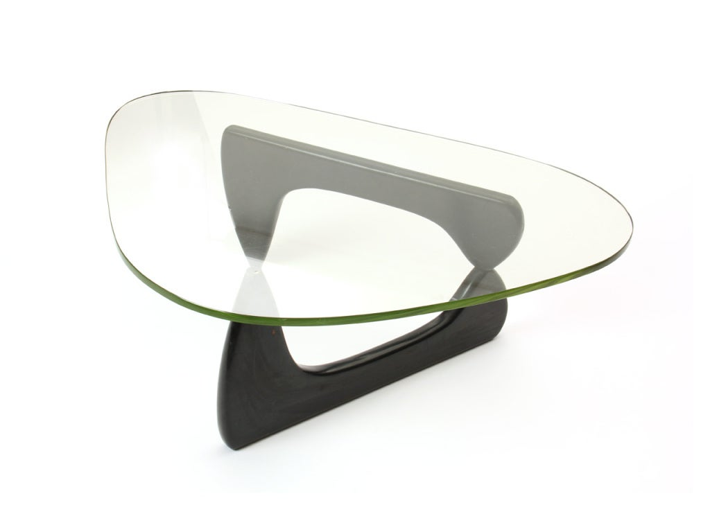 An early IN-50 low table having a triangular shaped thick glass top resting on a pivoting base.