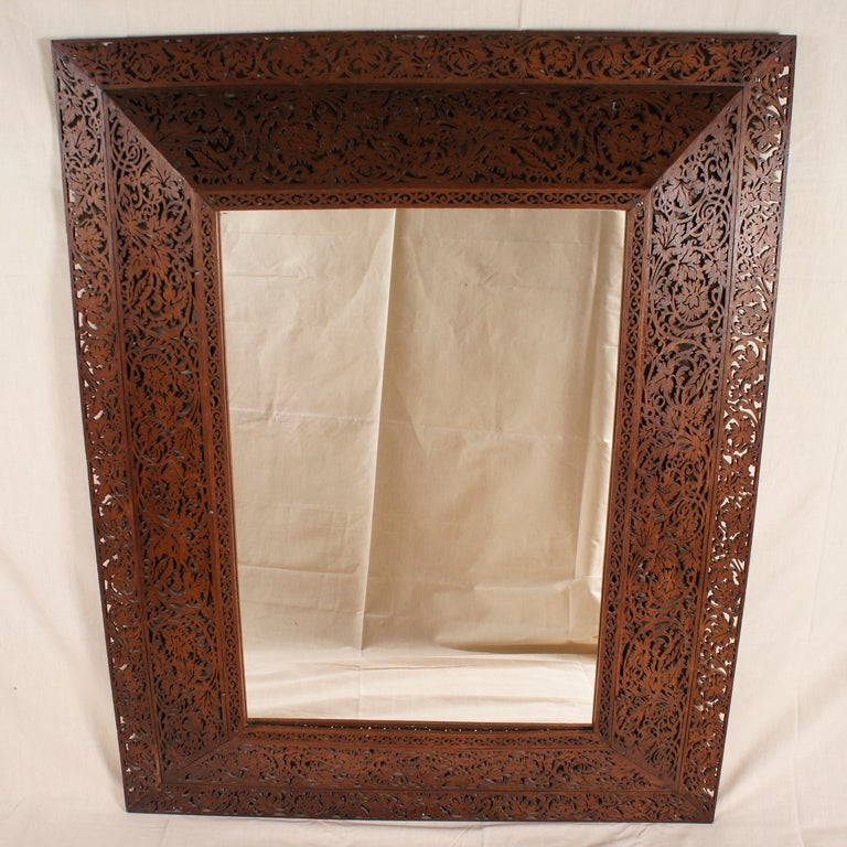 Lovely, ornate wooden mirror with intricate, foliage scrollwork detaling.