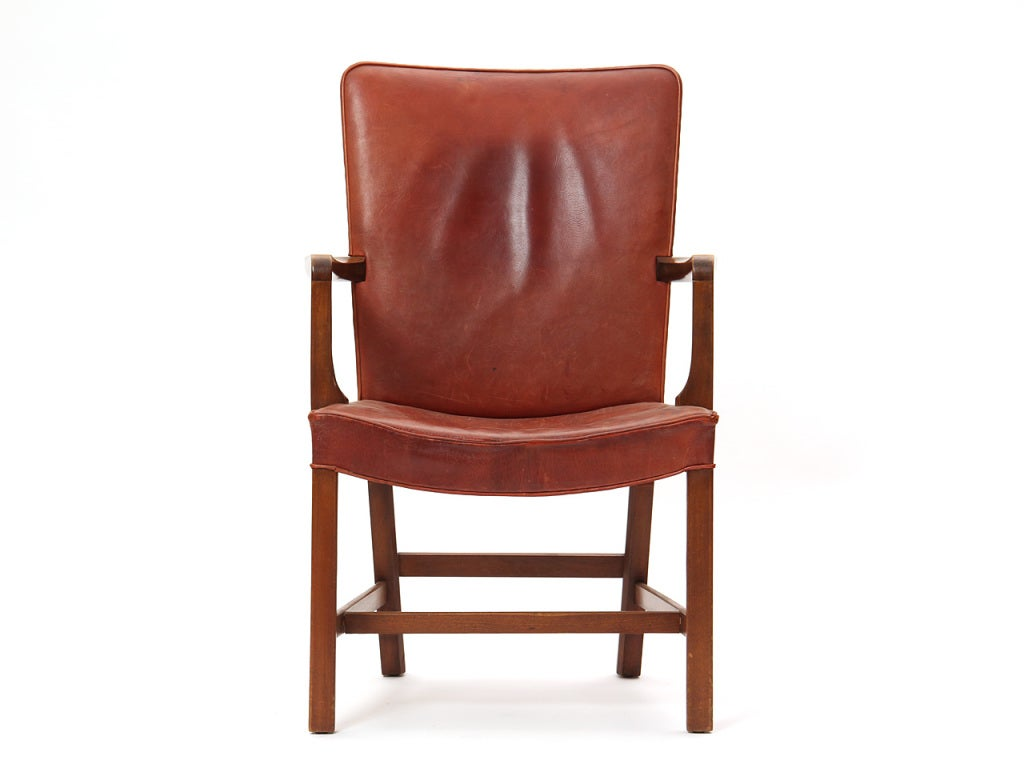 An elegant Scandinavian Modern armchair / side chair designed by Kaare Klint featuring Cuban mahogany and the original natural leather upholstery. Made in Denmark by Rud Rasmussen circa 1940s. Original Rud Rasmussen tag still attached underneath.