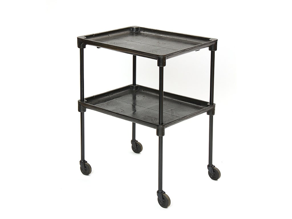 A patinated cast iron industrial cart on casters, with a