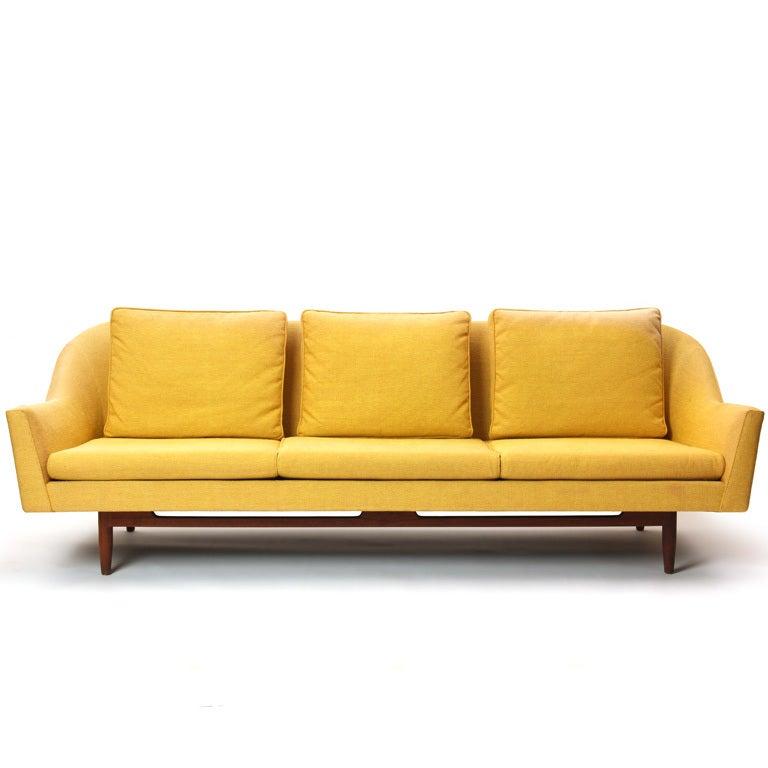 A three (3) seat sofa on a teak frame base retaining the original yellow upholstery.