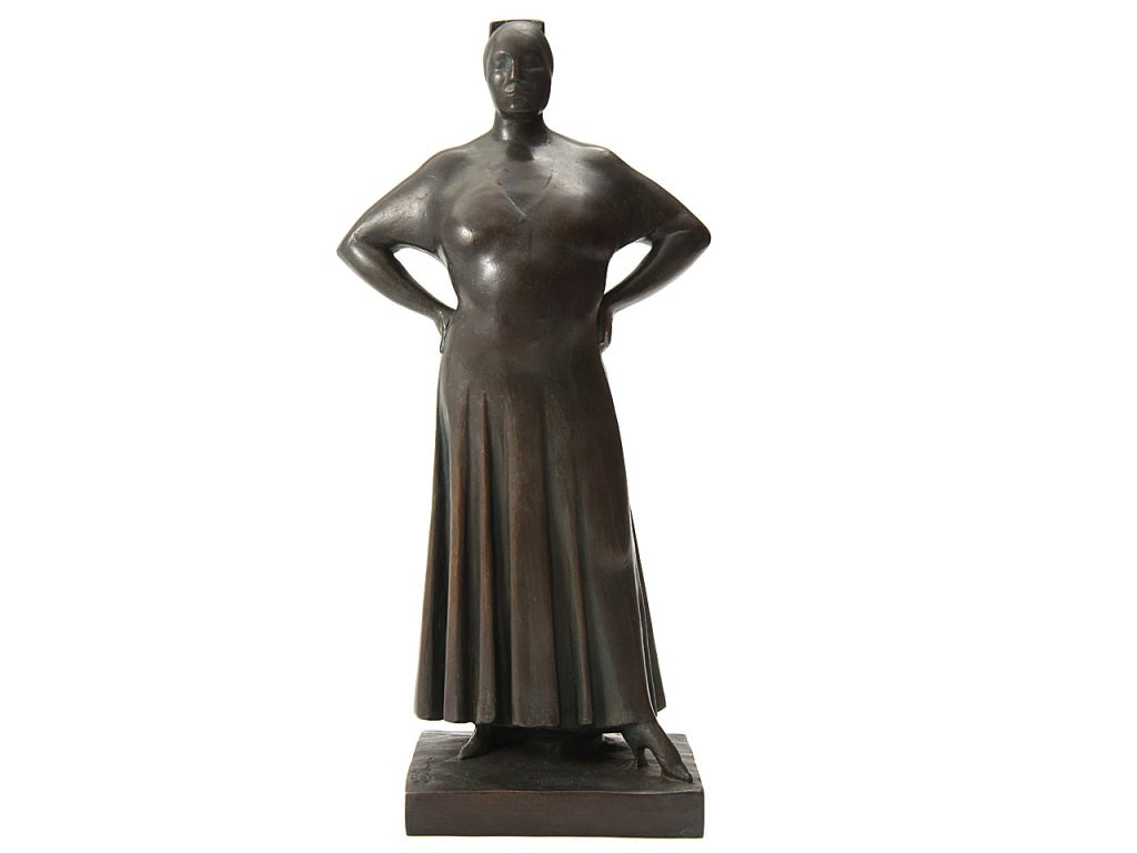 A bronze sculpture of a woman standing arms akimbo.