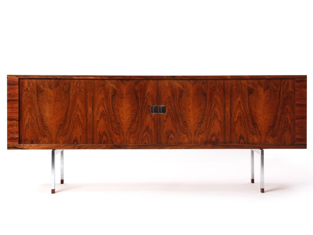 A rosewood credenza with two nearly invisible tambour sliding doors, enclosed, four shelves, and two adjustable trays on square chrome legs with rosewood feet.