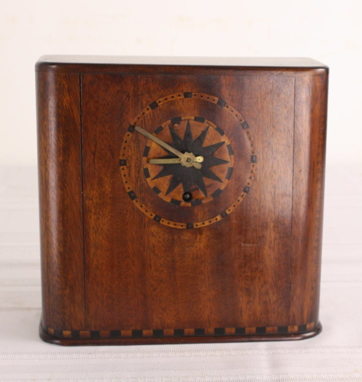 A very stylish Art Deco clock. Intricate marquetry along the top and bottom of the piece and around the clock face. Original brass key and interior works. Long running and quite accurate.