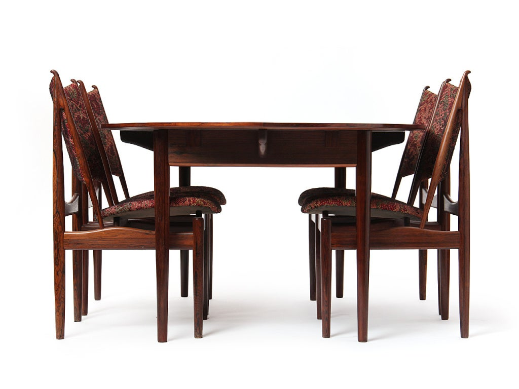 "A rosewood dining table with an oval top on tapered dowel legs. Including two 21"" extensions."