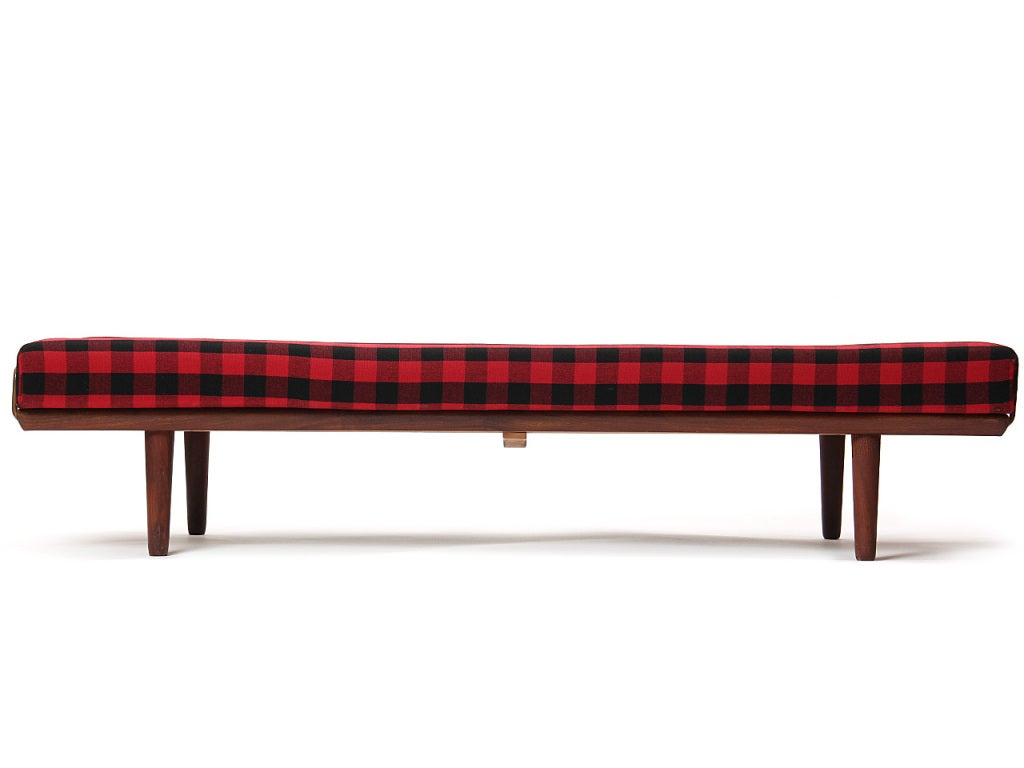 A teak daybed with brass rails to hold the cushion in original plaid wool upholstery.