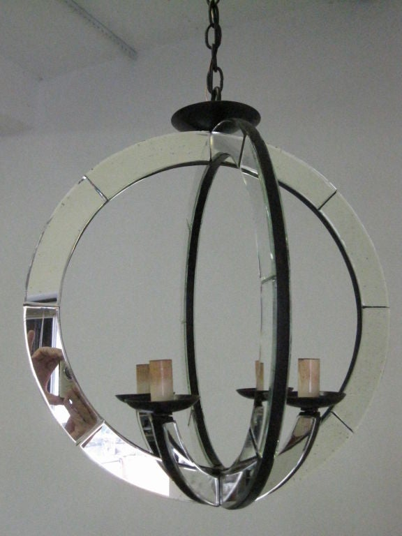 Chic pair of Italian Mid-Century style mirrored pendants / chandeliers consisting of antiqued mirrored spheres interspersed with four antiqued mirrored arms creating a sober, open and modern look. 