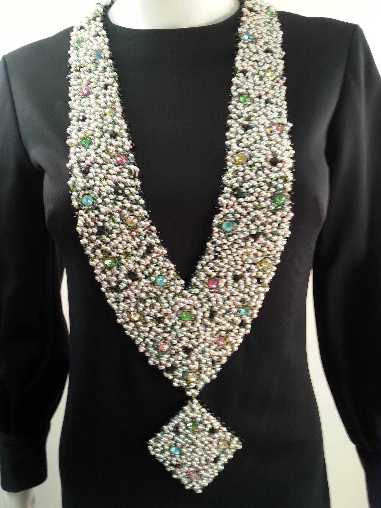 Luxurious black knit dress with show stopping tromp l'oeill necklace. Necklace is made of encrusted tiny pearls and pastel crystals embellished atop the fabric. Necklace wraps around the neck, past the waist, ending with a large diamond pendant.