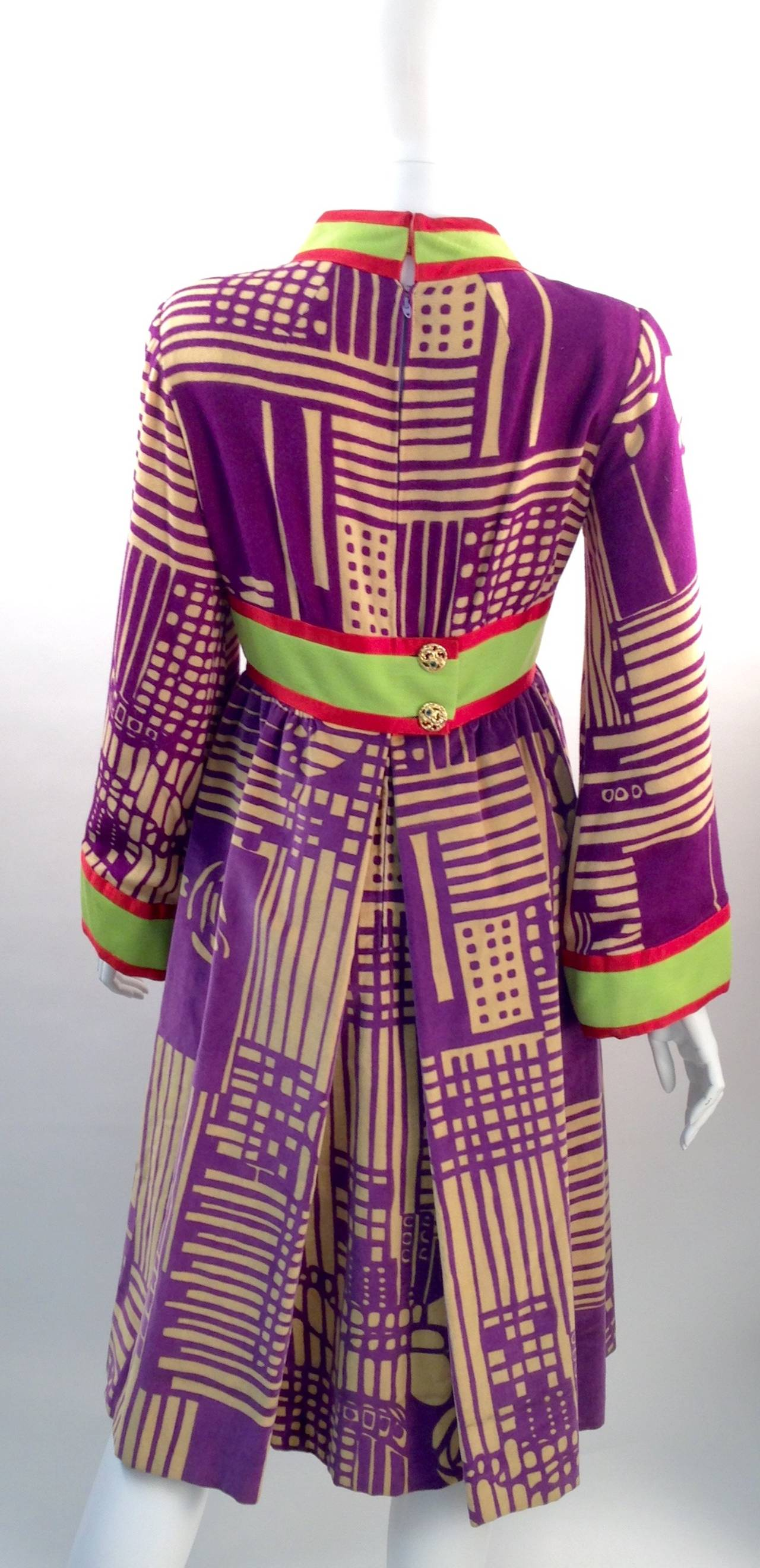 What a piece of work!  This dress has an fantastic mix of matching printed fabrics and colors! The bodice is a printed wool blend with purple abstract geometric shapes and flower patterns on a simple