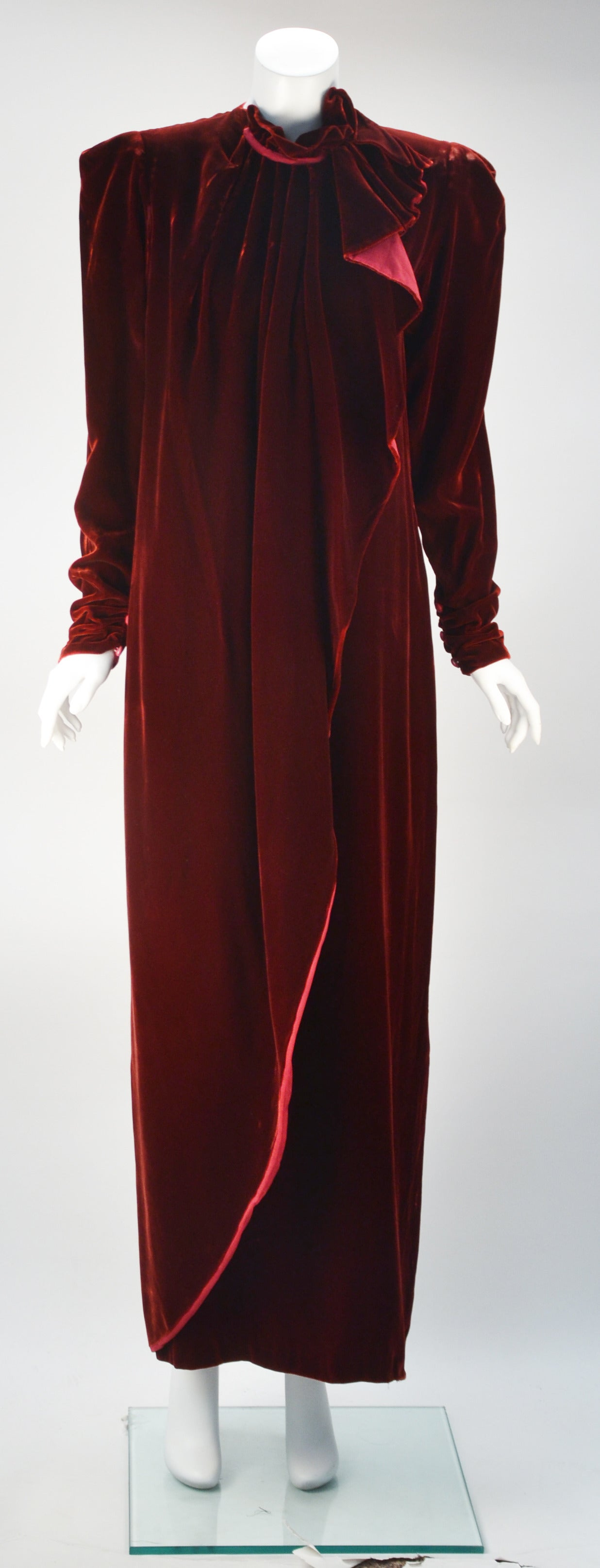 1980's GIORGIO DI SANT' ANGELO wine velvet gown features a unique ruffled detail at the neck that livens a familiar shape. Front zipper is covered by an exciting Drape/flounce that tapers to the hem lined with a bright wine organza. Rushing at the