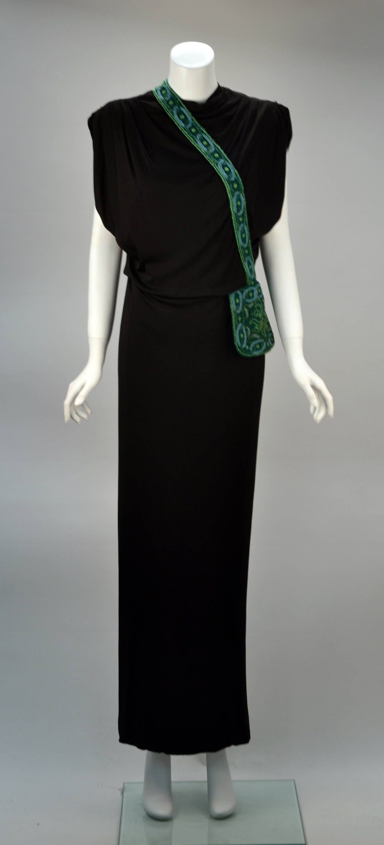 Long black dress with trompe l'oeil beading appears as a purse lying across this gorgeous bodice and sleekly atop the left hip. The beading dazzles in glorious hues of green and blue. Beautifully draped arm holes. High neck. Sophisticated fit and