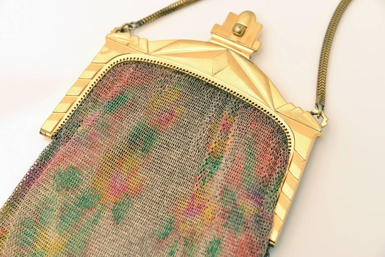Highly collectible Whiting and Davis mesh purse. This hand bag features painted mesh with an Edwardian/Art Deco frame and a yellow silk satin lining with inside pocket and round gold mirrior. The flower motif is yellow, orange, pink and red on both
