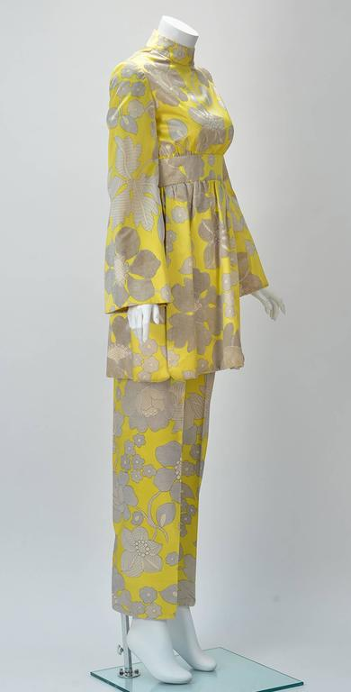 One of a kind 1960's George Halley tunic and pant set. Tunic is yellow with grey and white flowers. Random velvet grey flowers throughout. Mock turtle neck, long bell sleeves, Defined empire waistband with gathers. Two slits on the side of the