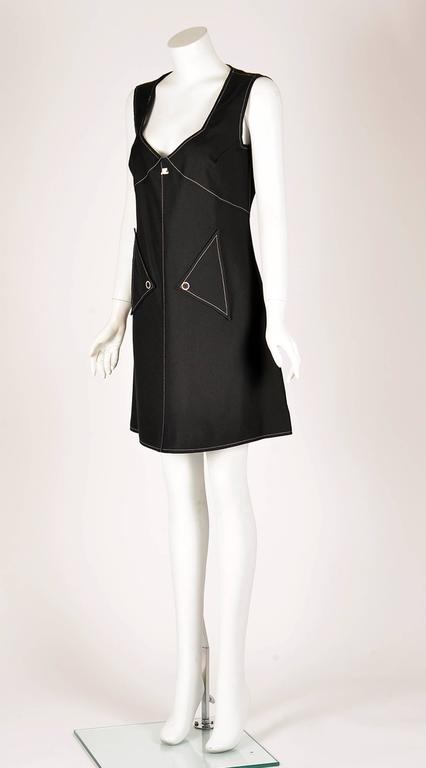 1980s does the 60s with this wonderful Courreges day to evening dress. A loose A-line black rayon dress has a sweetheart neckline and contrasting white stitching. The dress has two triangle pockets in the front, with a single button closure, as well