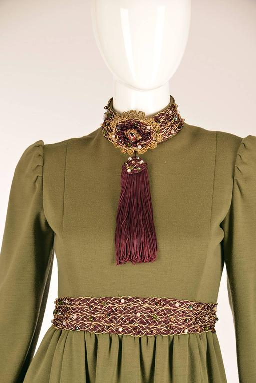 Late 1960s Geoffrey Beene olive green dress. High neck, long sleeves, and plum and gold braided thread looped together to form a chain around the neck, wrist, and waist. Three braids in total on the neck, wrist, and waist. Beading throughout the