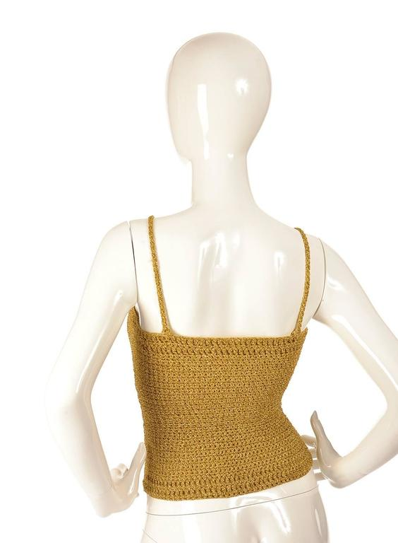 Fun and girly gold knit metallic crop top. This top is tightly knitted together in a weave pattern, using gold yarn with metallic gold thread interspersed through out the top. The top has spaghetti straps, and can be pulled over the head.
