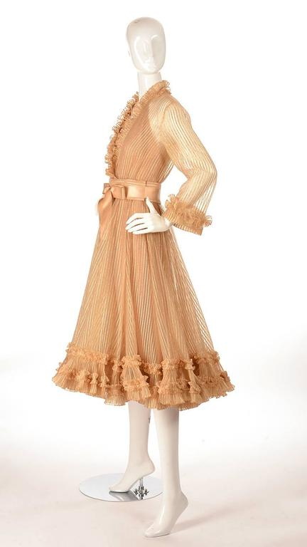 "This stunning, immaculately preserved 1973 Fall/Winter cocktail dress was designed by Marc Bohan for Christian Dior. The dress is numbered ""01917"". The A-line tea length dress is composed of delicate chiffon with interwoven gold threads,"